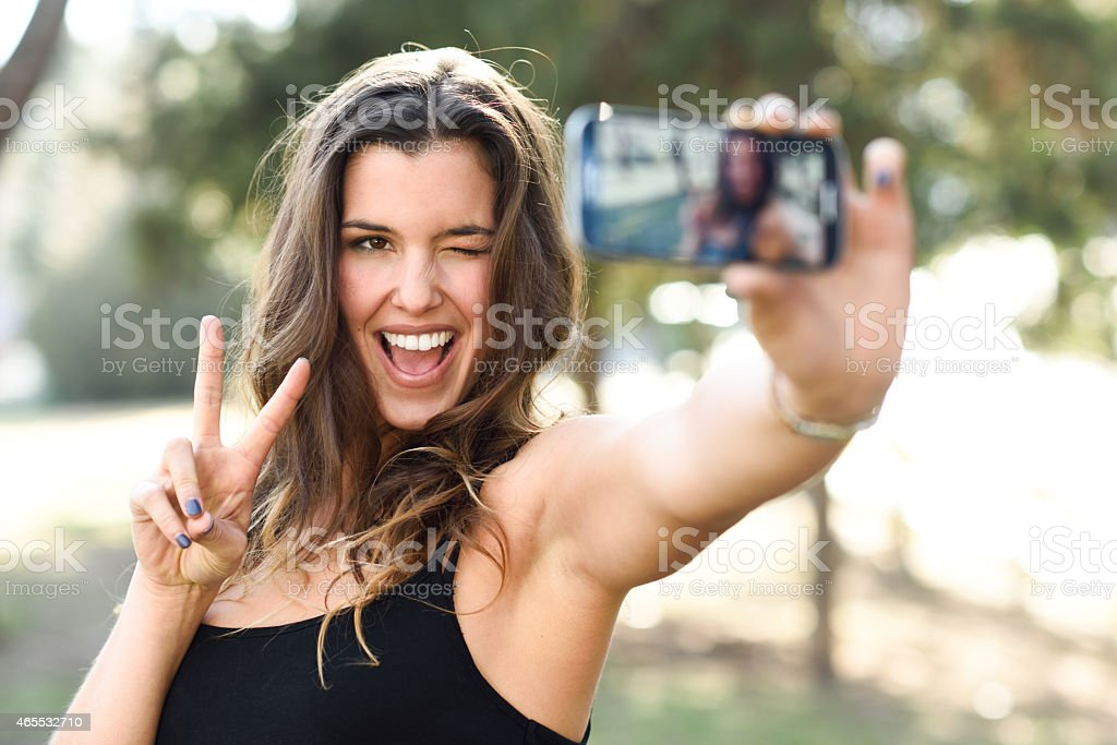 Young woman taking selfie in park with phone stock photo