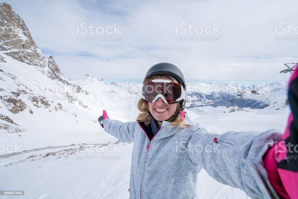 Young woman taking selfie in ski slope, Switzerland stock photo