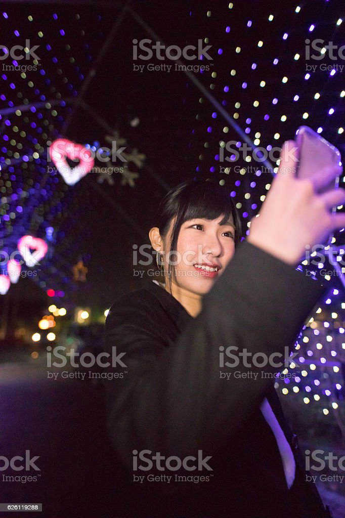 Young woman taking selfie picture in Christmas lights stock photo