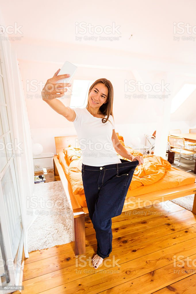 Young woman taking selfie showing weight loss stock photo