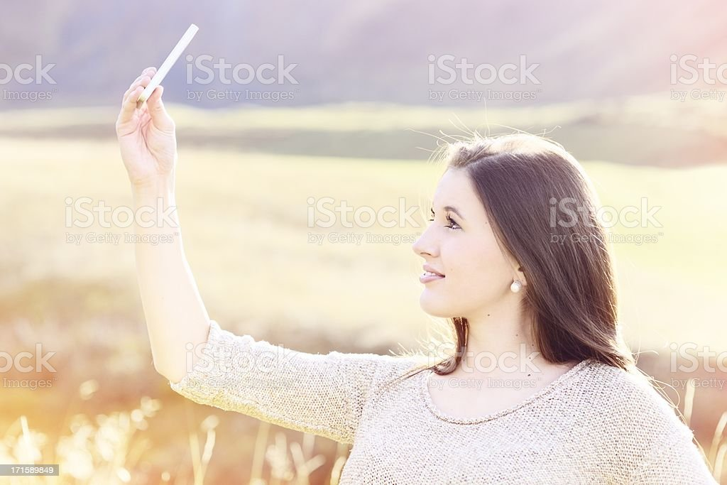 Young Woman Taking Self-Portrait Outdoors royalty-free stock photo