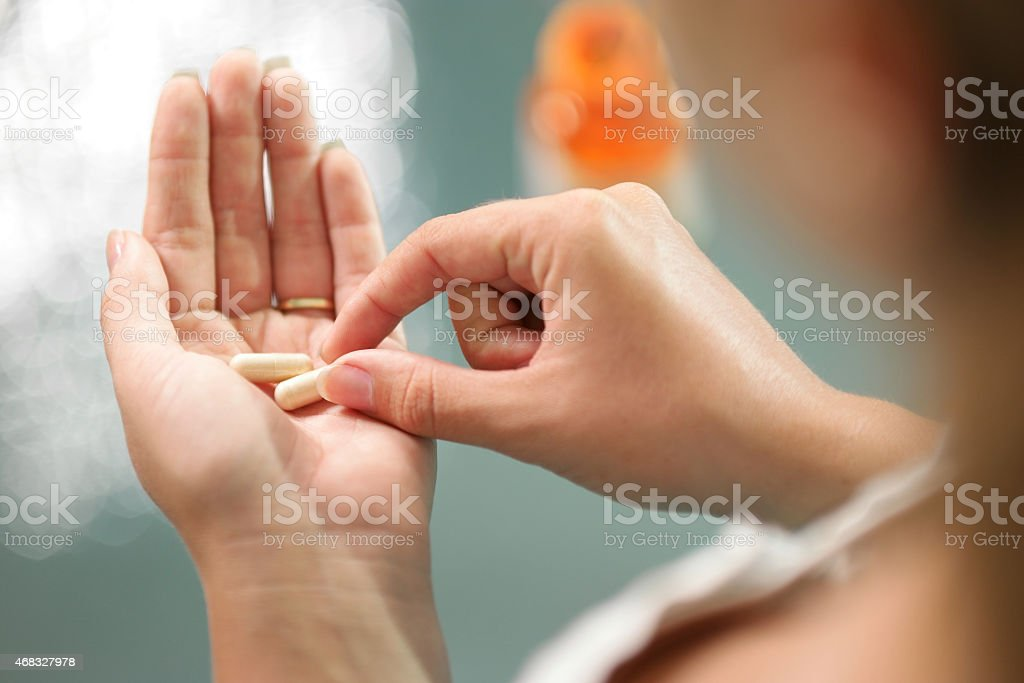 Young woman taking vitamins ginseng pill stock photo