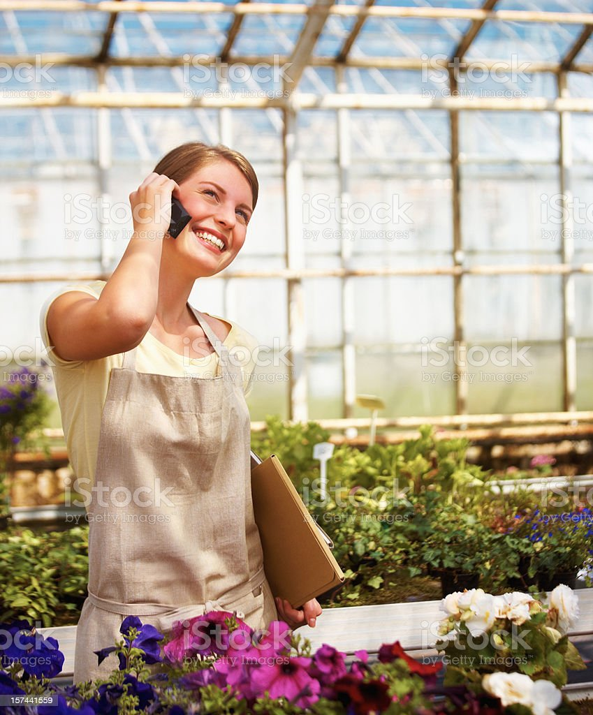 Young woman talking on cellphone in plants nursery royalty-free stock photo