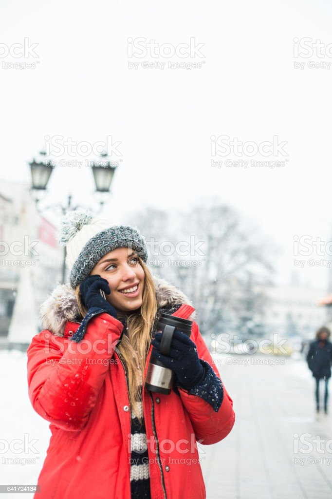 Young woman talking on her cellphone while walking stock photo