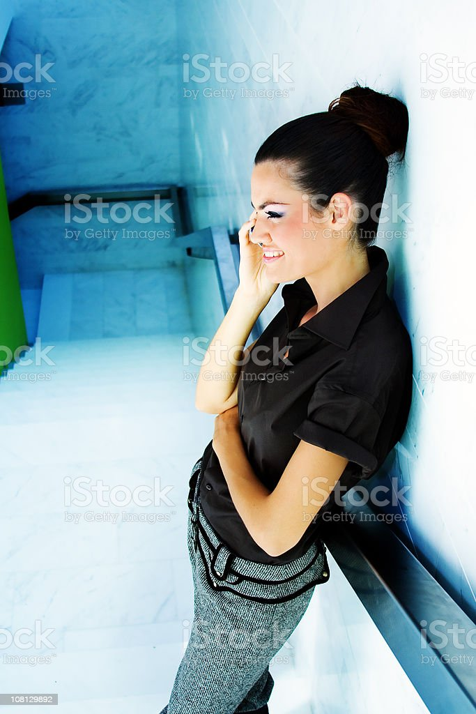 Young Woman Talking on Mobile Phone in Staircase royalty-free stock photo