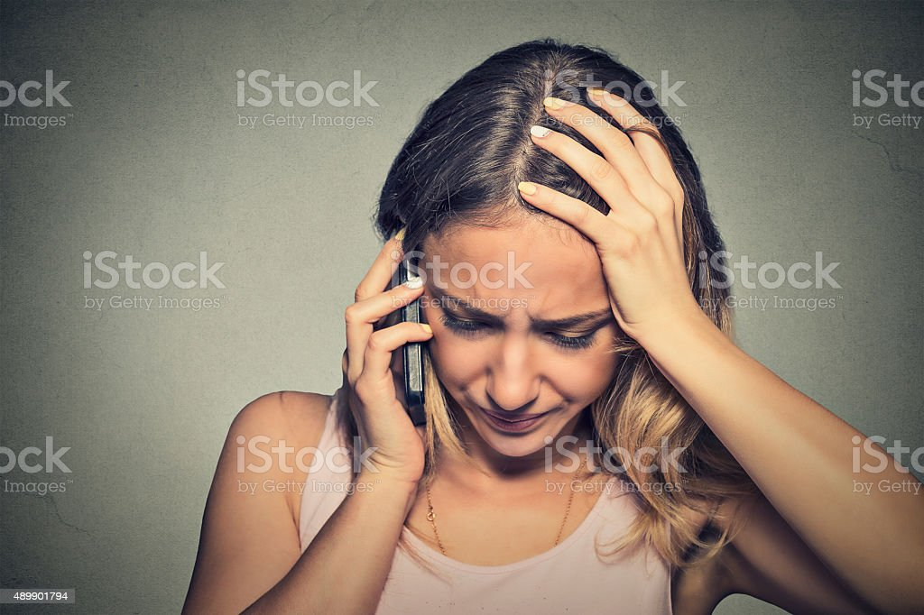 young woman talking on mobile phone looking down stock photo
