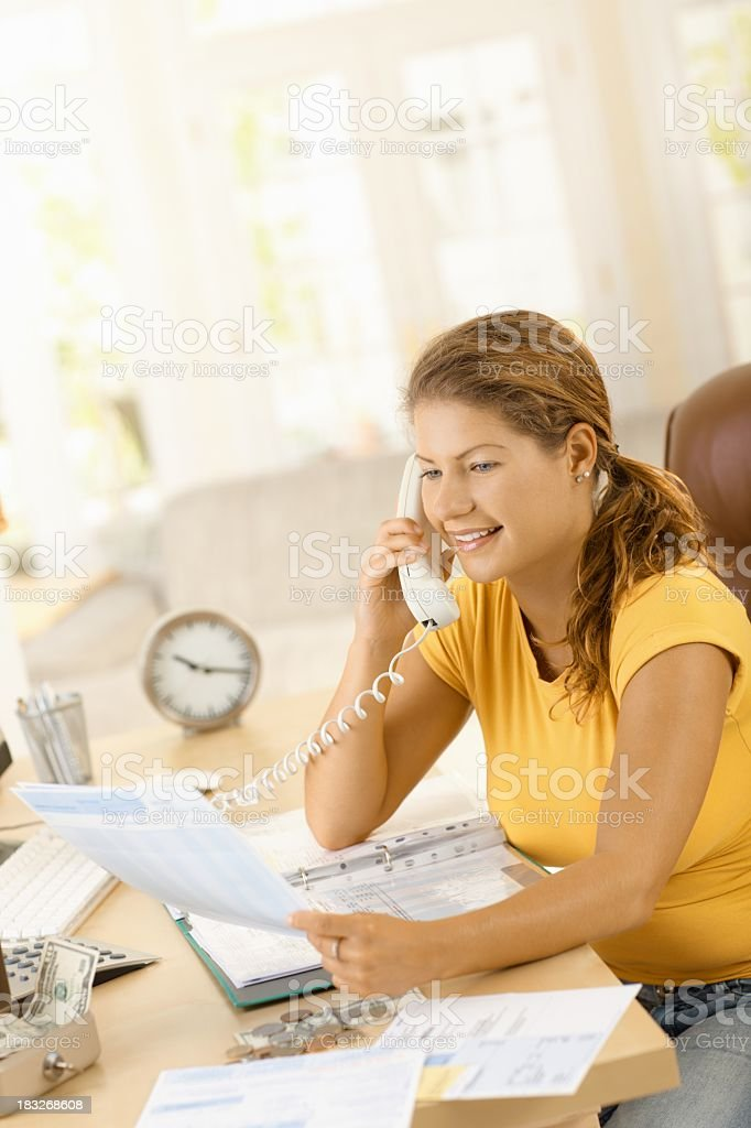 Young woman talking on phone about finances royalty-free stock photo
