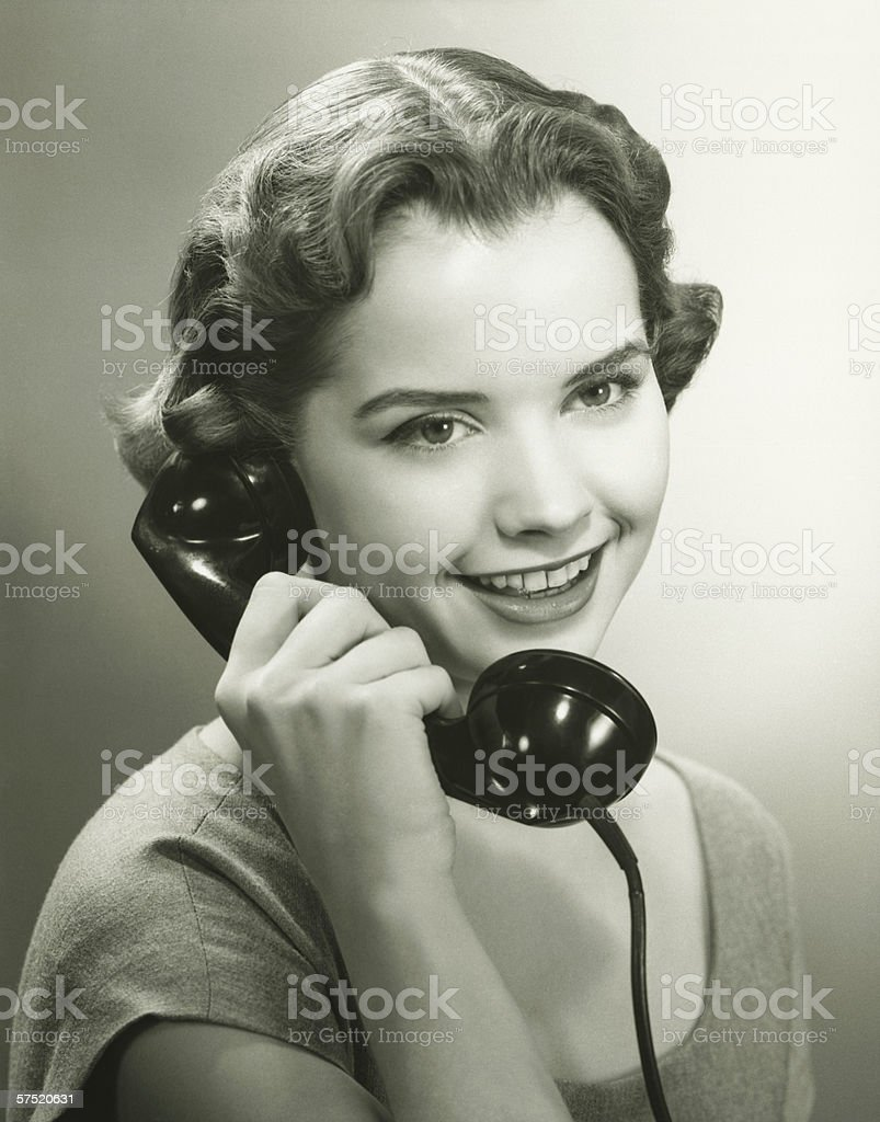 Young woman talking on phone in studio, (B&W), portrait stock photo