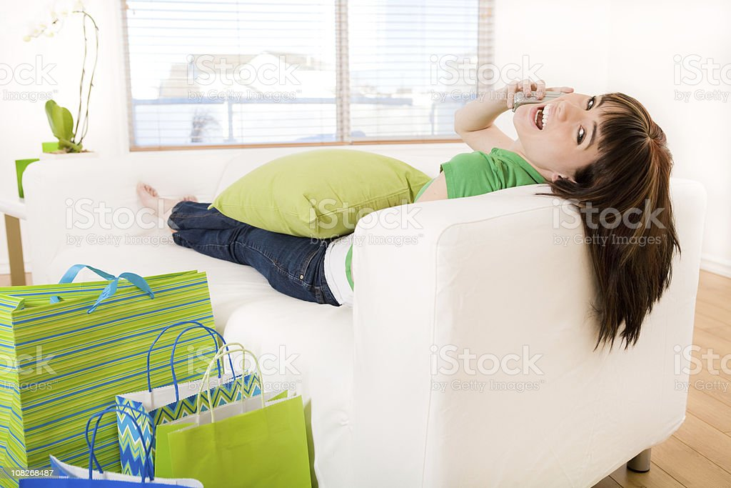 Young Woman Talking on Phone Surrounded by Shopping Bags royalty-free stock photo