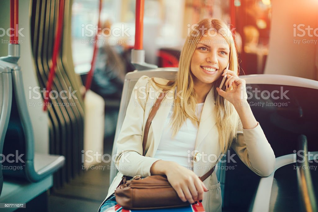 Young Woman Talking on the Phone In Public Transportation stock photo