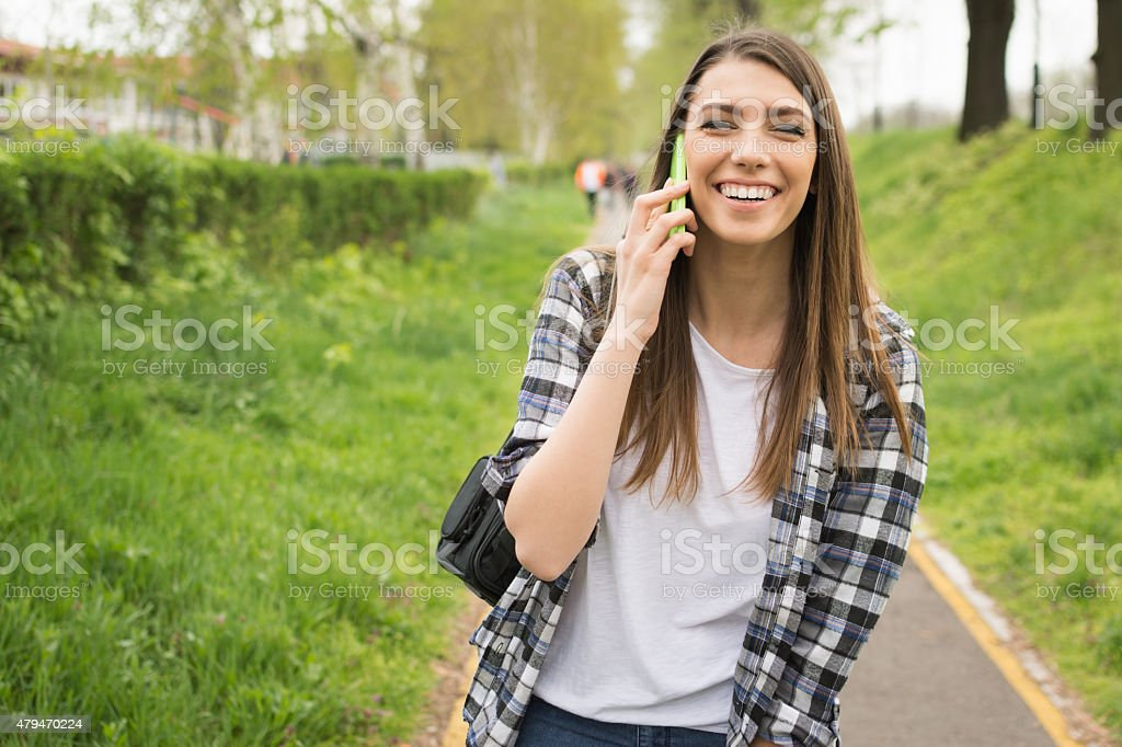 Young woman talking on the phone laughing. No retouch stock photo