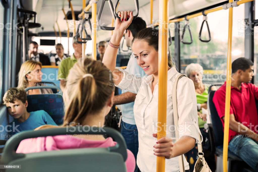 Young woman talking to her friend on bus. stock photo