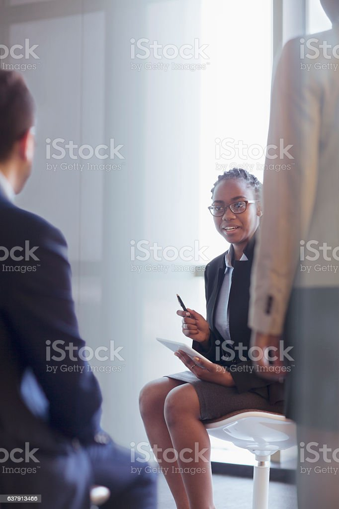 Young woman talking with colleagues in meeting stock photo