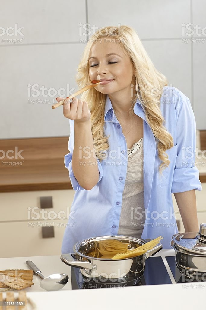 Young woman tasting spaghetti sauce in kitchen stock photo