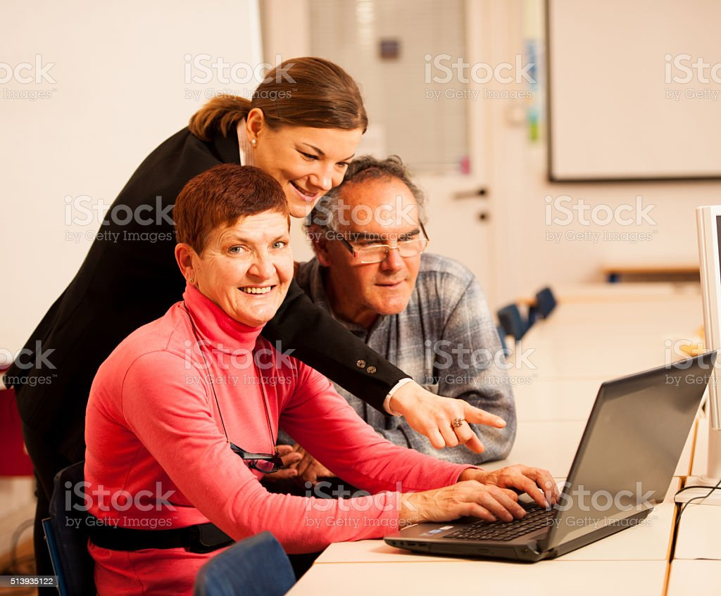 Young woman teaching elderly couple of computer skills. stock photo
