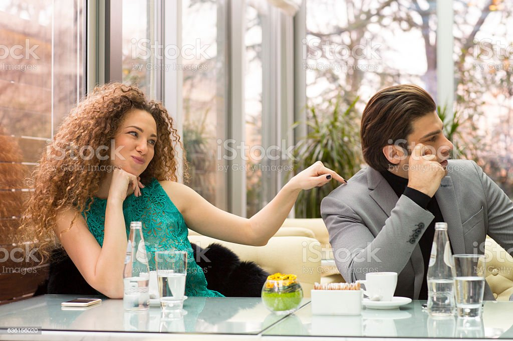 Young woman teasing sulking boyfriend stock photo