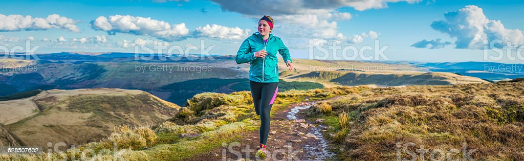 Young woman teenager trail running along mountain ridge path panorama stock photo