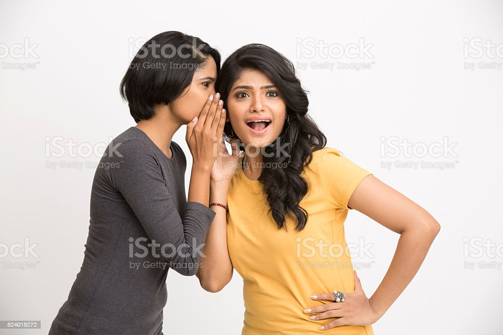 Young woman telling secrecy news to her surprised girlfriend stock photo