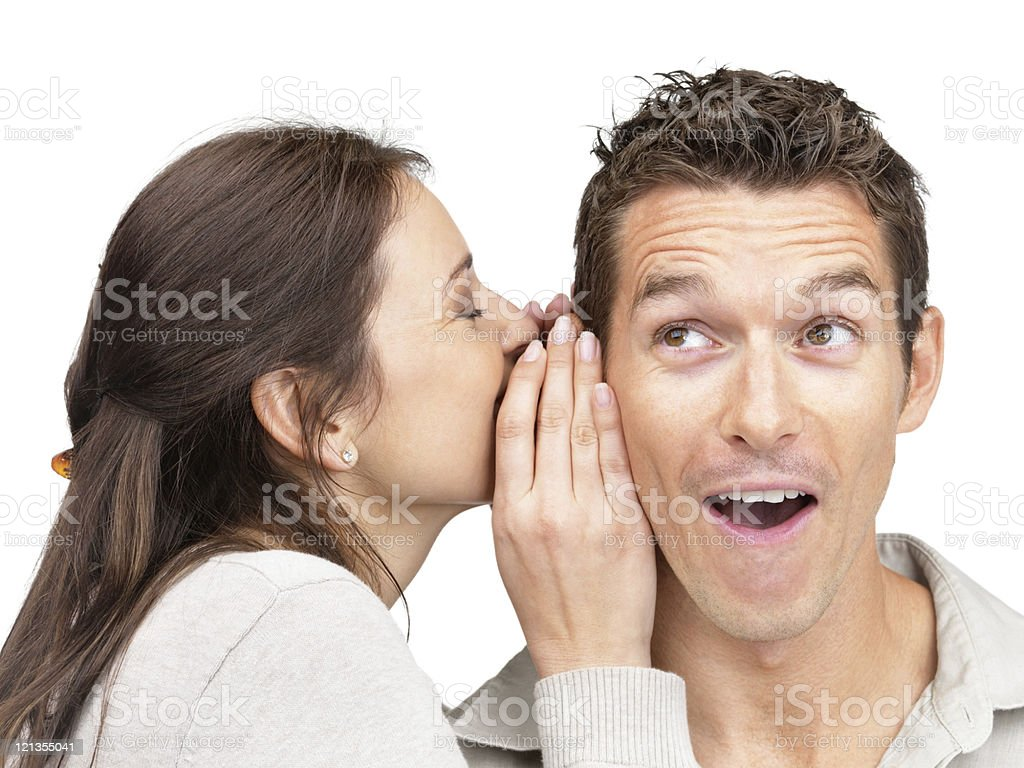 Young woman telling secret to a man stock photo