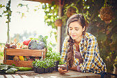 Young woman text messaging at organic farm