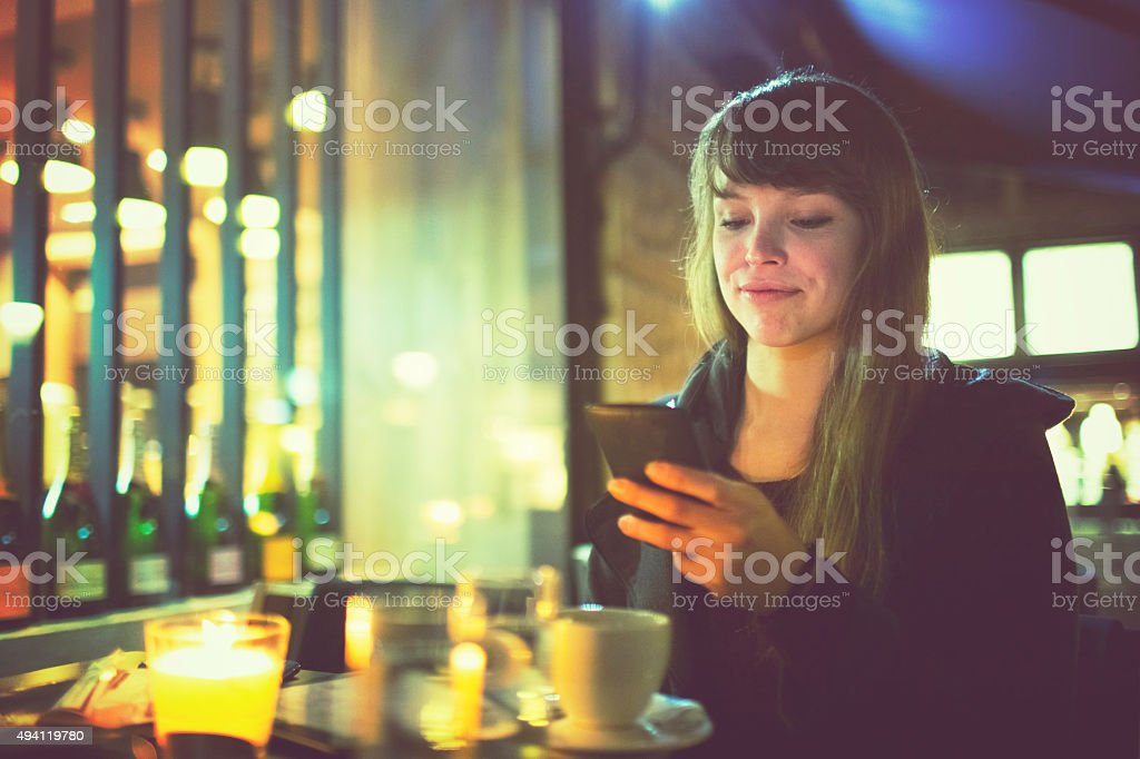 Young woman text messaging in outdoor cafe stock photo