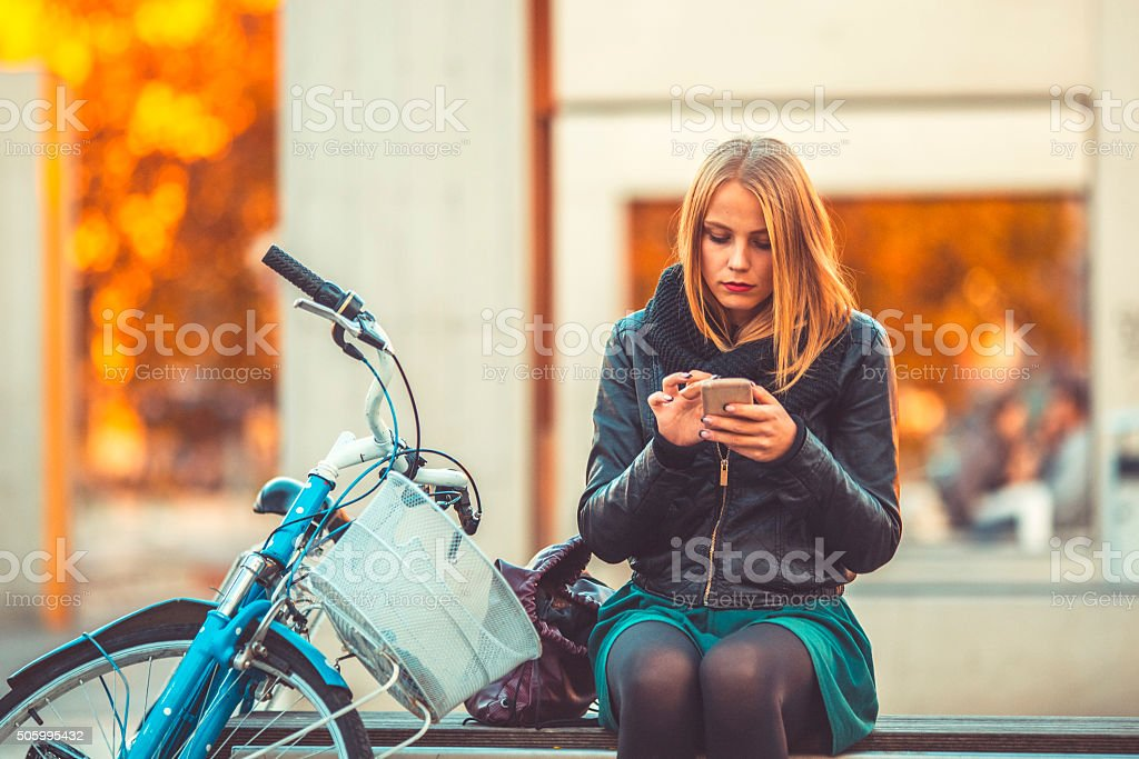 Young woman text messaging in the city stock photo