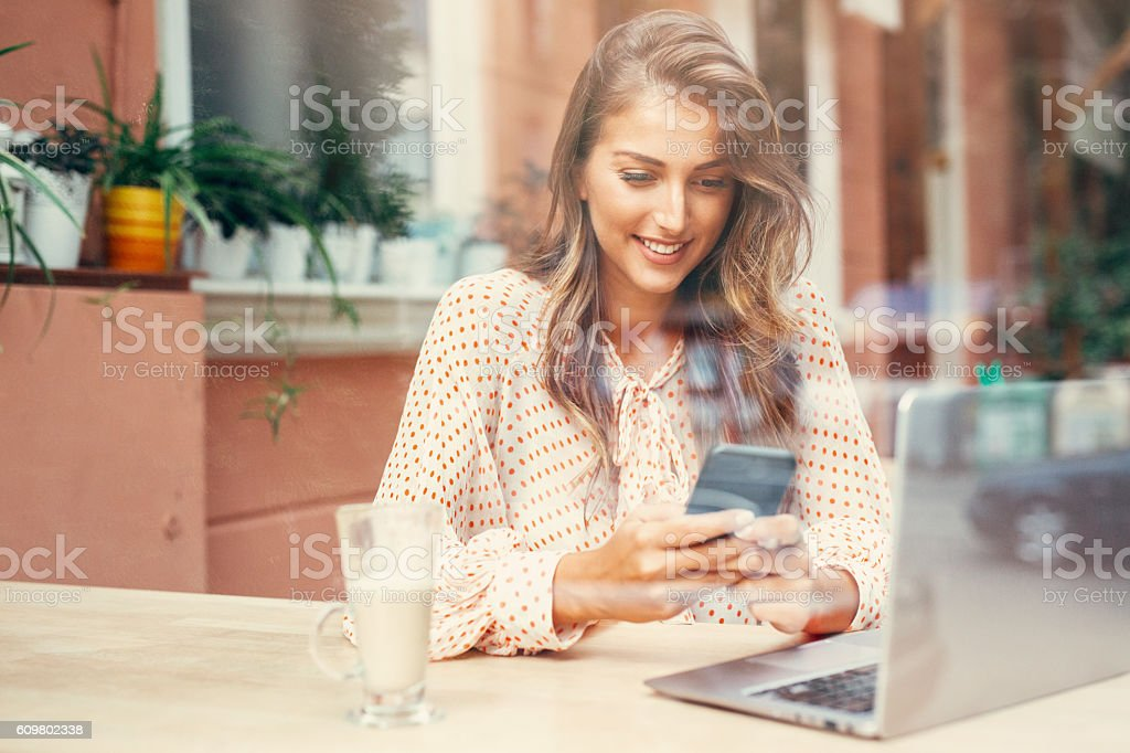 Young woman texting at the cafe stock photo