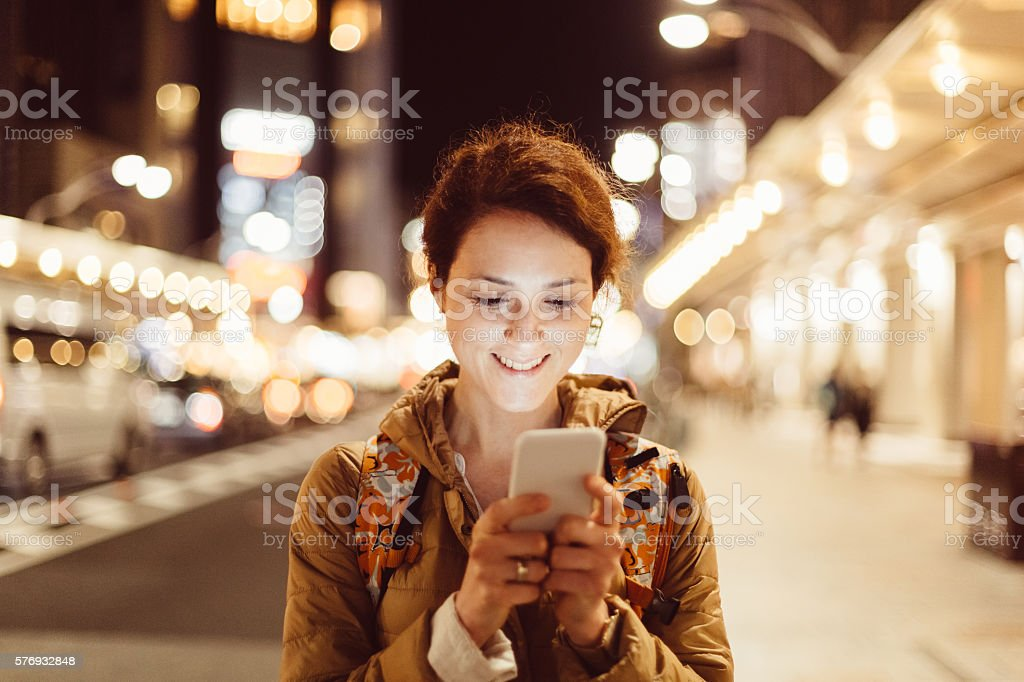 Young woman texting for Uber stock photo