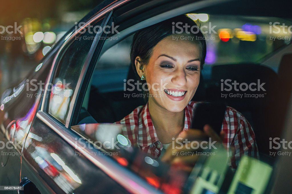 Young woman texting in a car at night stock photo