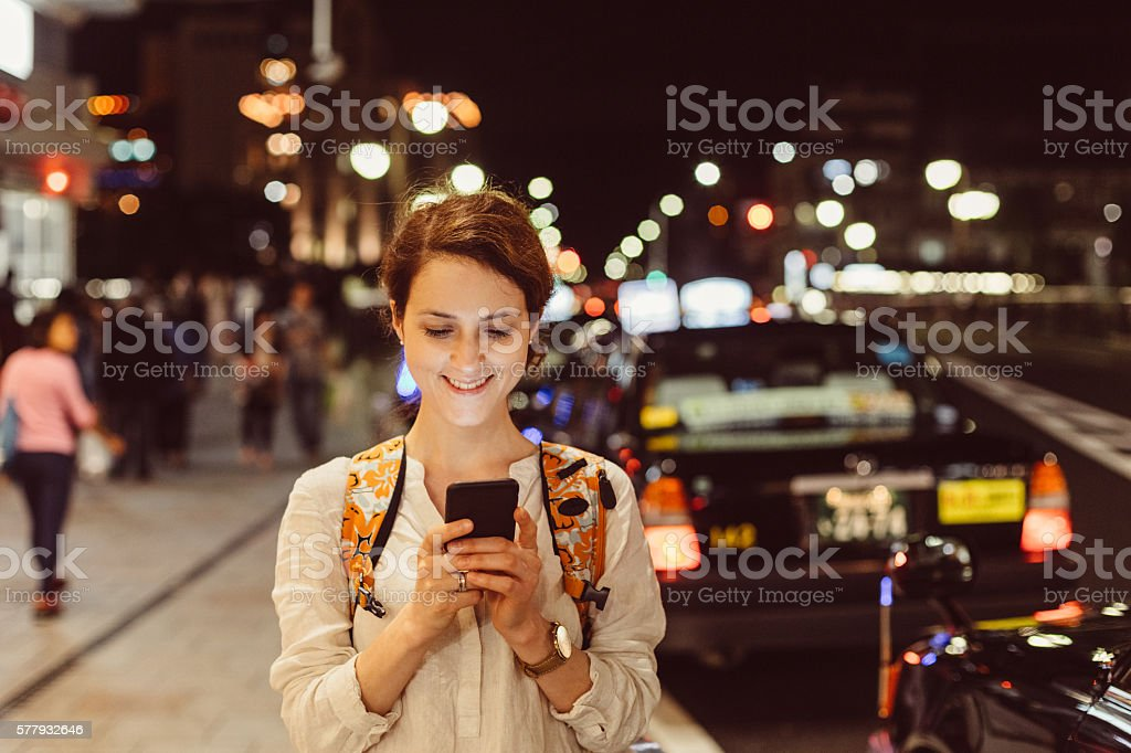 Young woman texting in the city stock photo