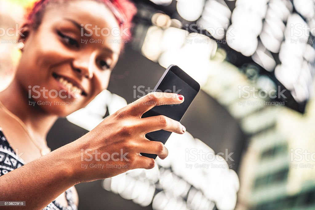 Young woman texting in Times Square stock photo