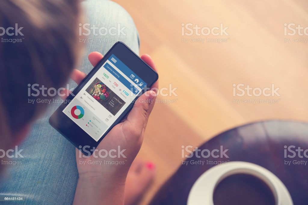 Young woman texting on a mobile phone with coffee stock photo