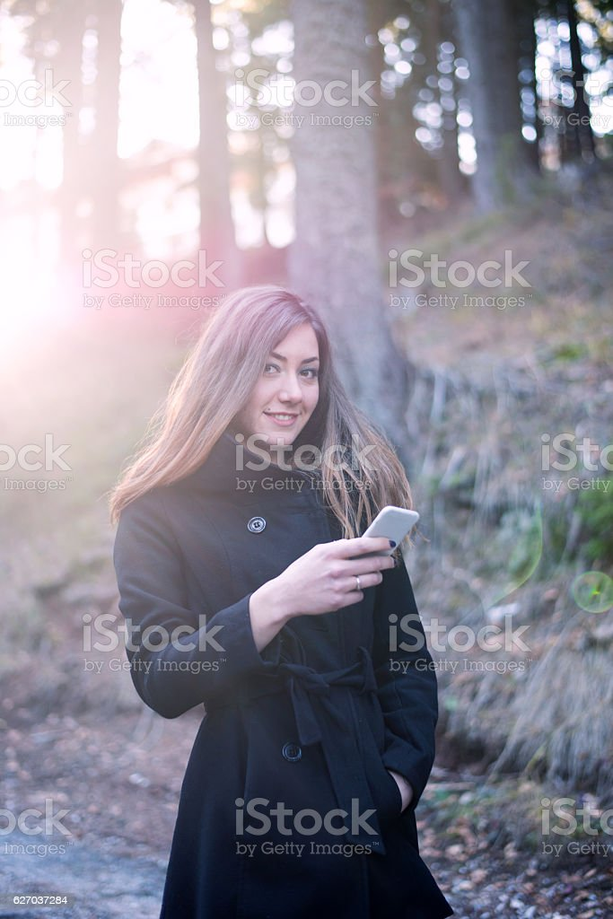 Young woman texting on her mobile in a woodland setting. stock photo