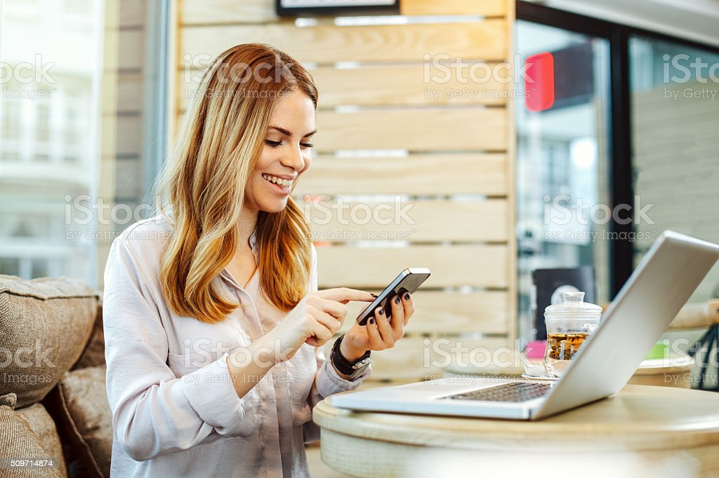 Young woman texting on the phone in a cafe stock photo