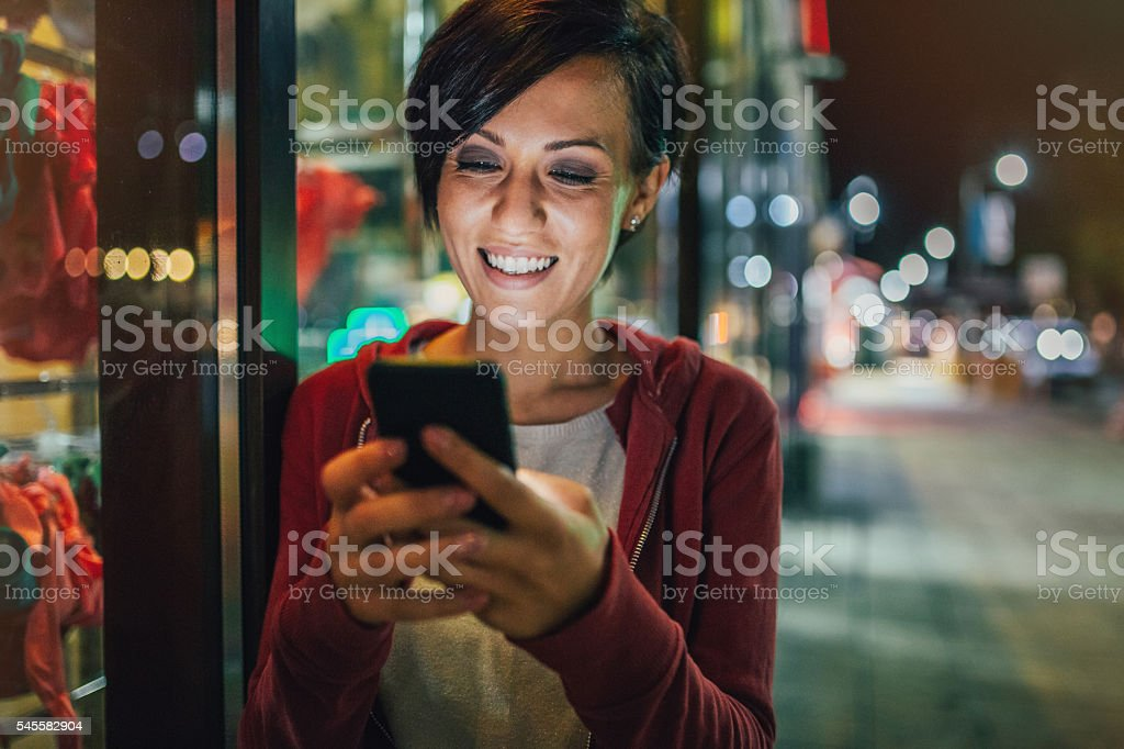 Young woman texting on the street at night stock photo