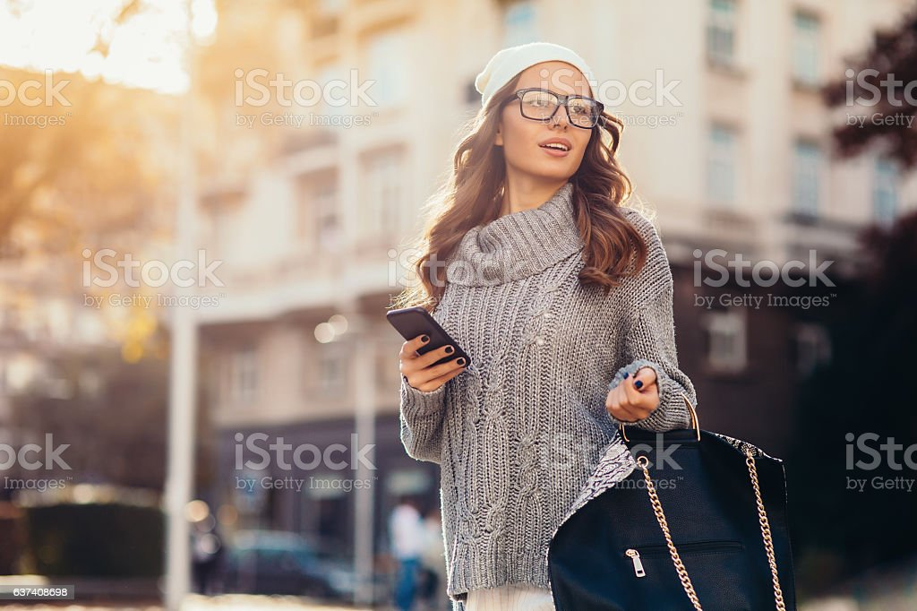 Young woman texting outdoors stock photo