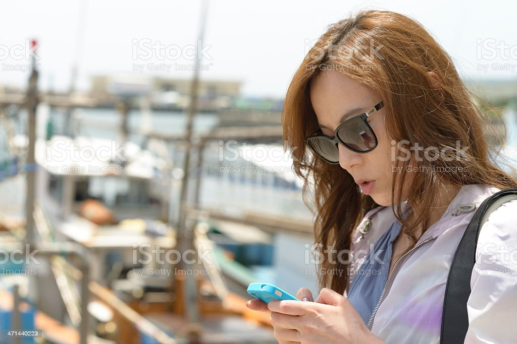 Young woman textmessaging in the sea port stock photo