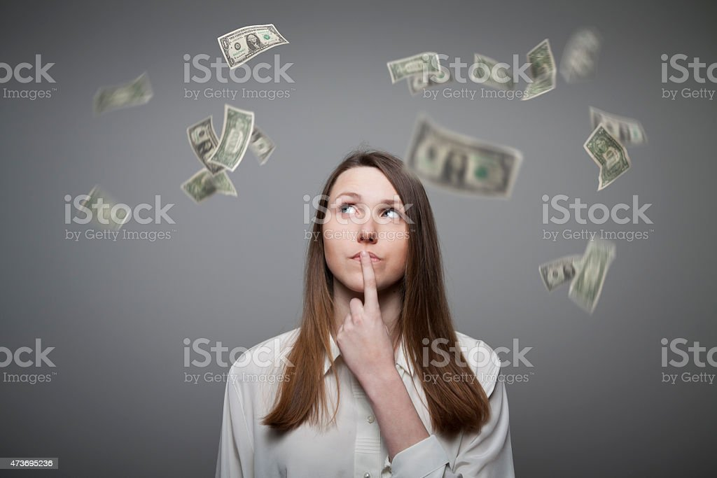 Young woman thinking about dollar bills flying stock photo