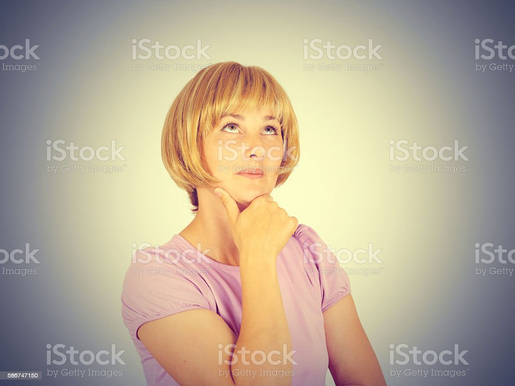 Young woman thinking looking up stock photo