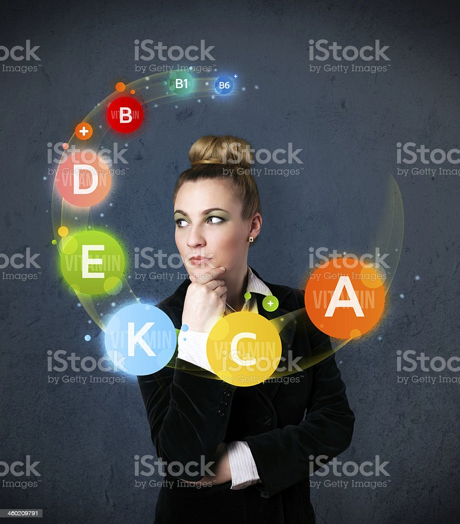 Young woman thinking with vitamins circulation around her head stock photo