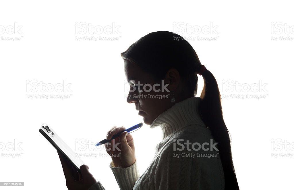 Young woman thoughtfully writes, draws, writes stock photo