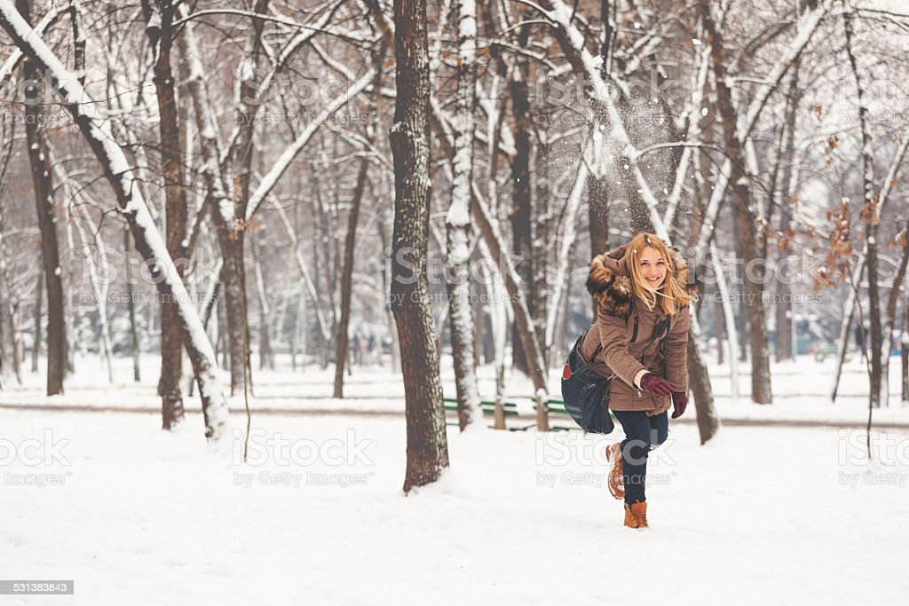 Young woman throwing a snow ball stock photo