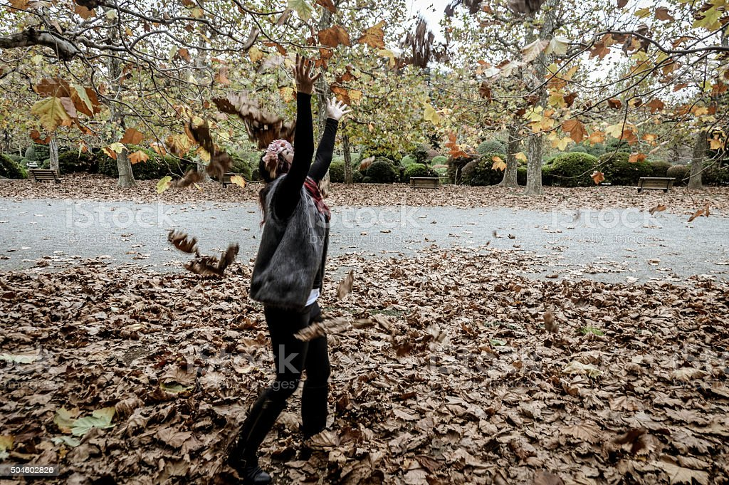 Young woman throwing autumn leaves in the air stock photo