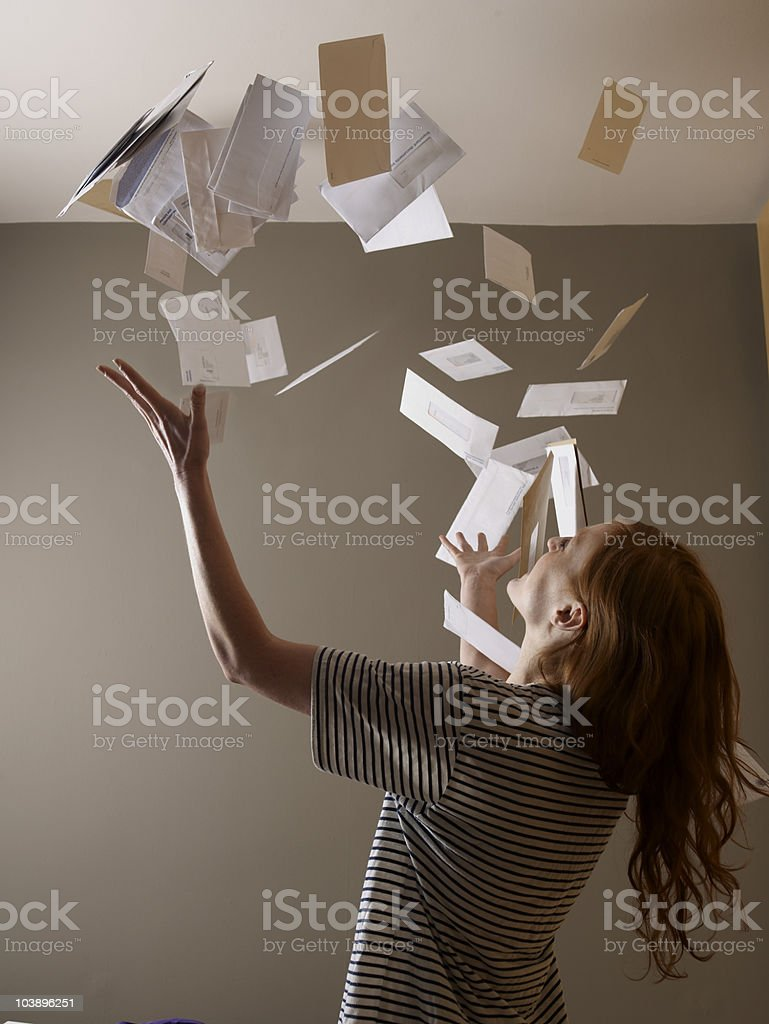 Young woman throwing bills in air stock photo