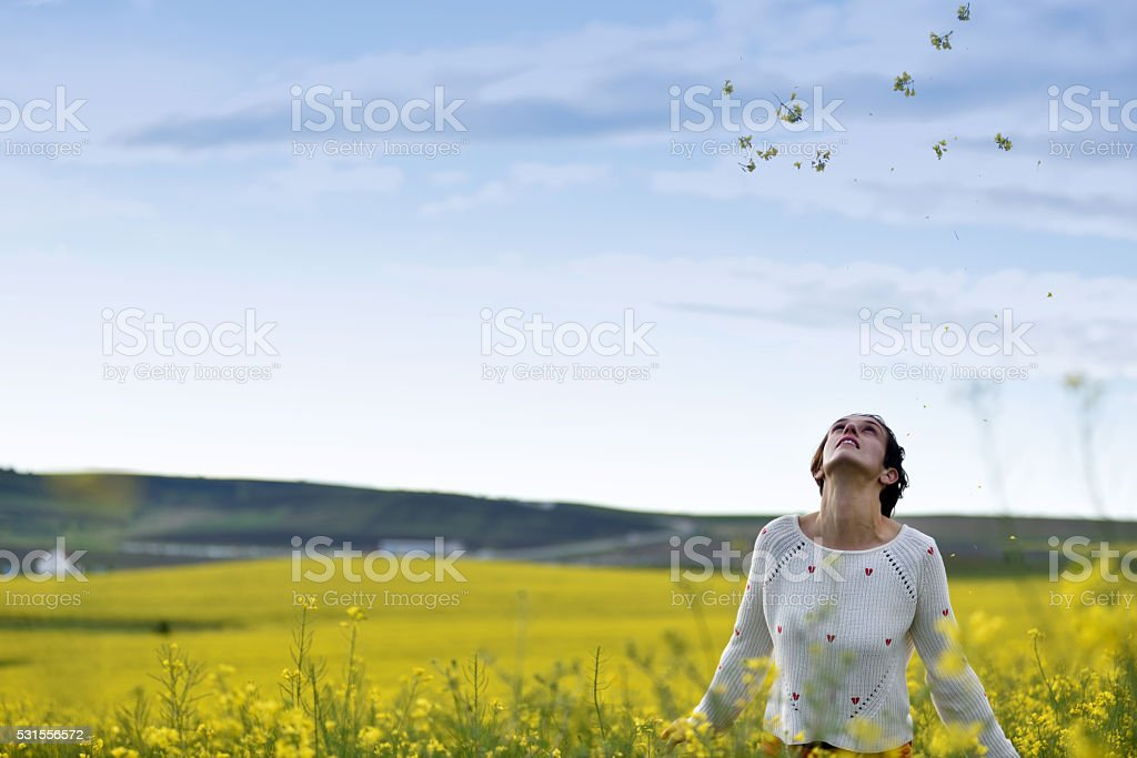 Young woman throwing yellow petals in the air stock photo