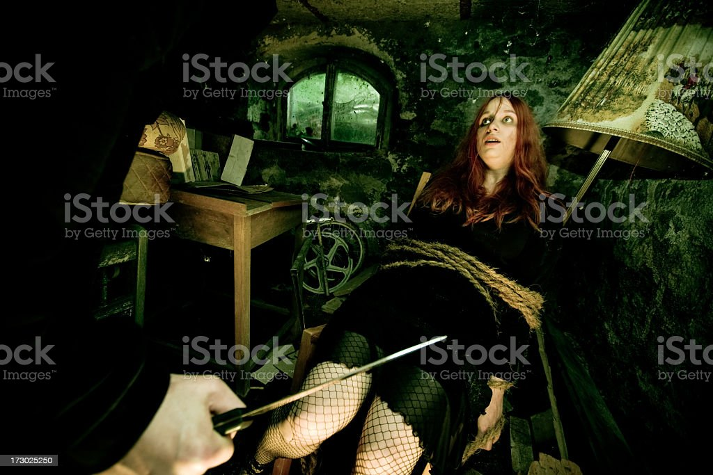 Young Woman Tied to Chair with Man's Hand Holding Knife royalty-free stock photo