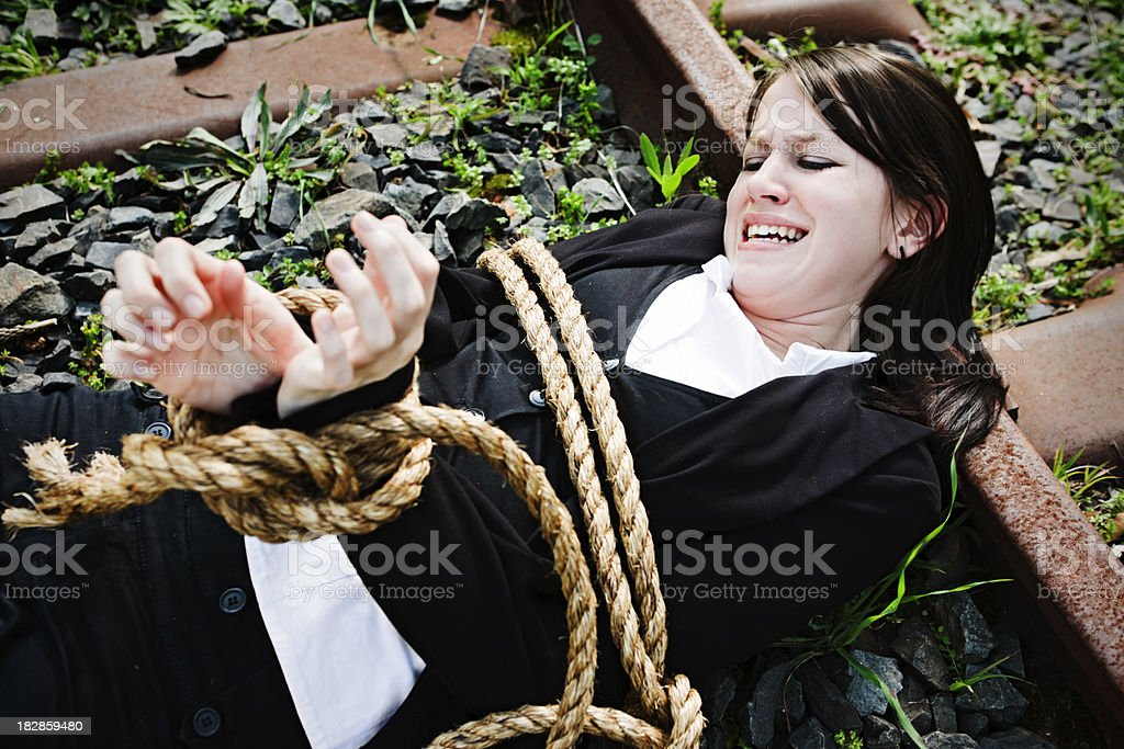 Young woman tied to railroad track struggles against  bonds stock photo