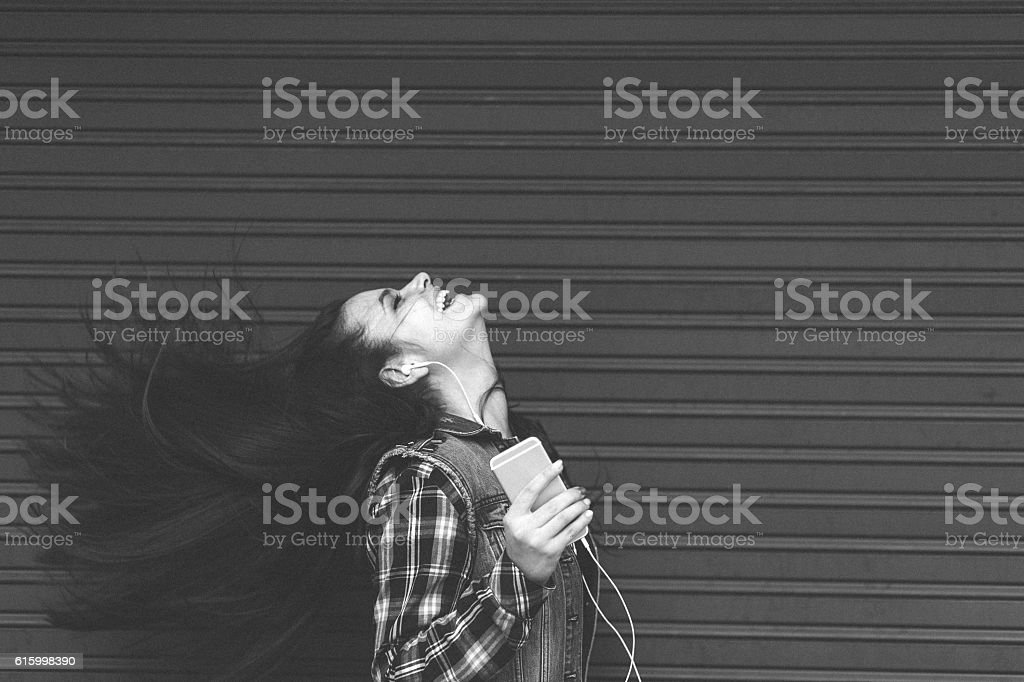 Young woman tossing hair and enjoying the music stock photo