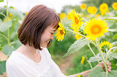 Young woman touching her forhead to sunflower with smile