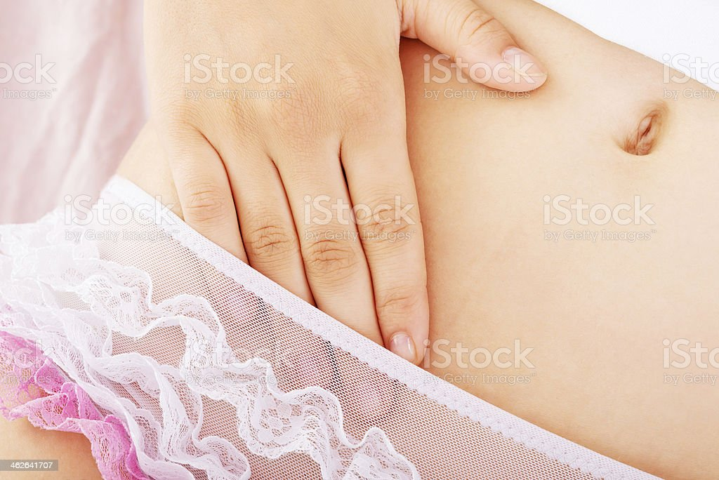 Young woman touching herself on  bed stock photo